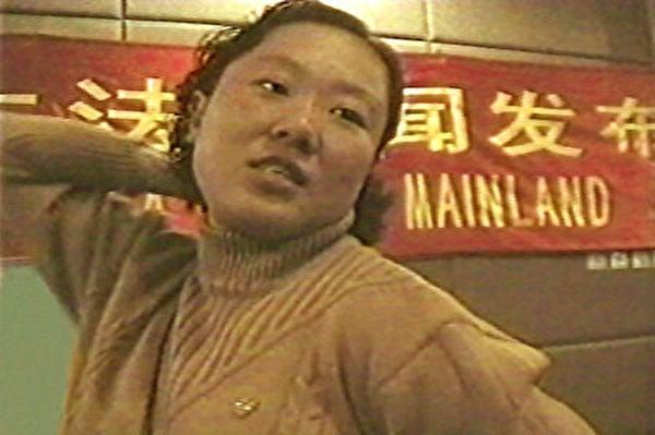 丁延在1999年10月28日北京新聞發佈會上,向記者描述警察用背銬的酷刑折磨學員。(明慧網)