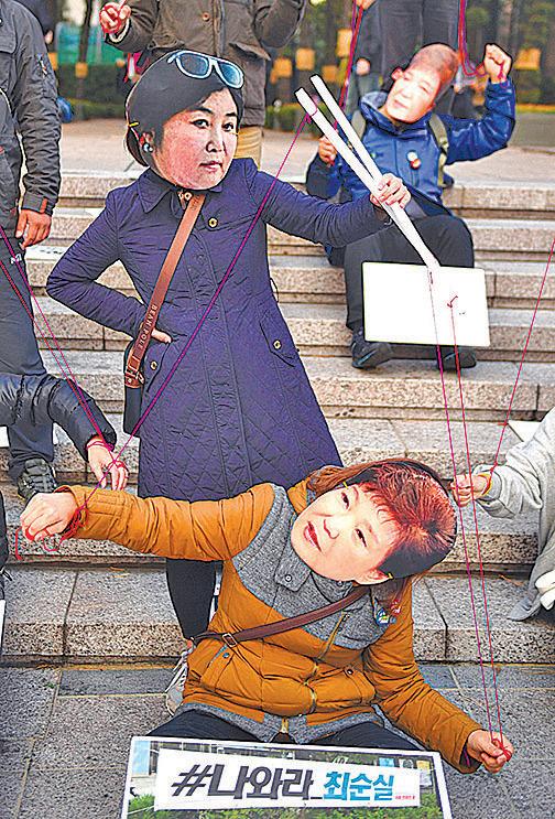 干政事件在南韓引起公憤,有民眾戴著崔順實(後)和朴槿惠(前)面具抗議。(Getty Images)