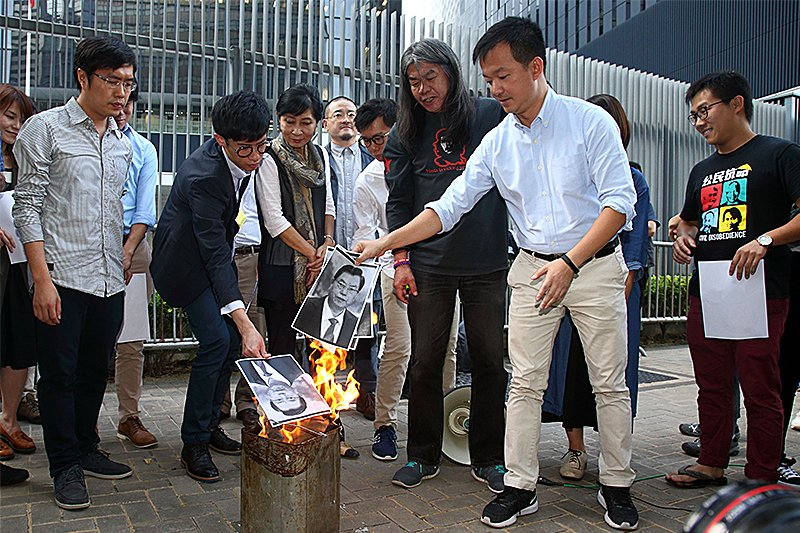 多位非建制派議員高喊「守護香港法治,反對人大釋法」,並一起燒毀人大委員長張德江的頭像,寓意反對人大釋法。(潘在殊/大紀元)
