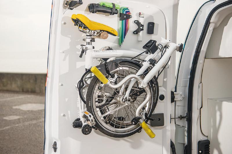 摺疊式單車安置在後門上,隨時可取下來使用。(網絡圖片)