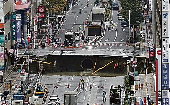11月8日清晨,福岡市JR博多站前的路面忽塌陷,路上出現兩個約長10米、寬15米的大洞。(AFP)
