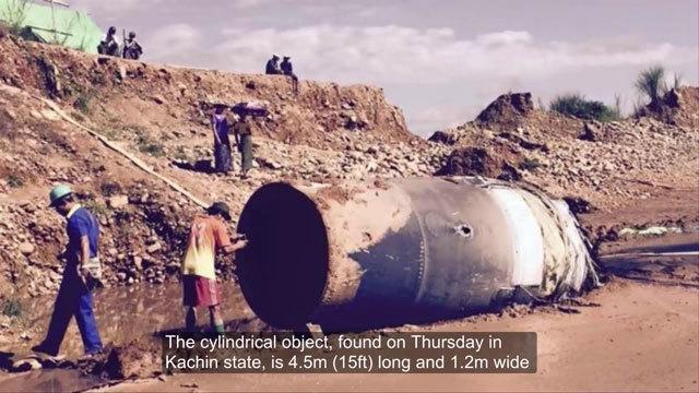緬甸國營媒體報道,周四,在緬甸北部一處玉石礦場,人們發現一個從天外掉下來的大型金屬筒狀物。(視像擷圖)