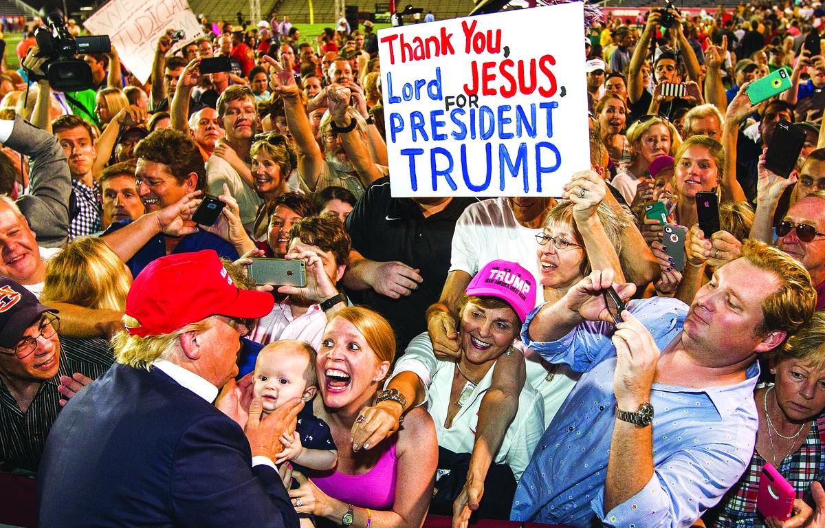 特朗普陣營在11月8日開票前曾樂觀地表示,看到特朗普的支持者排隊4、5個小時,只為了參加他的競選集會,沒有理由相信他們不會去投票——即使特朗普在發動投票方面幾乎沒有任何「地面戰術」。圖為特朗普(背影)和熱情的支持者在一起。(Getty Images)