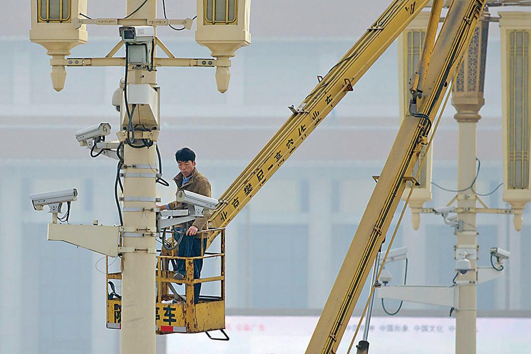 由中共做後盾營運的海康威視已成為全球監控設備最大供應商,其產品可能預留「後門」,對全球構成重大安全隱患。圖為2013年10月31日,一男子在北京天安門廣場檢查監視鏡頭。(Getty Images)