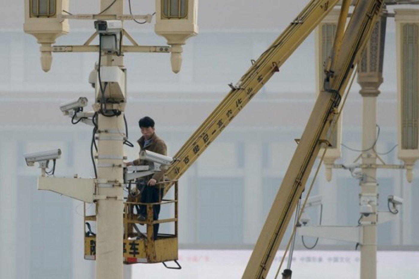 圖為一名男子於2013年10月31日在北京天安門廣場檢查監視鏡頭。(Ed Jones/AFP/Getty Images)