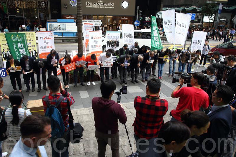 來自多個界別的民主派數十名候選人,昨日中午聚集在中環鬧市派發政綱。他們又鞠躬呼籲選民周日投票,支持他們)。(李逸/大紀元)