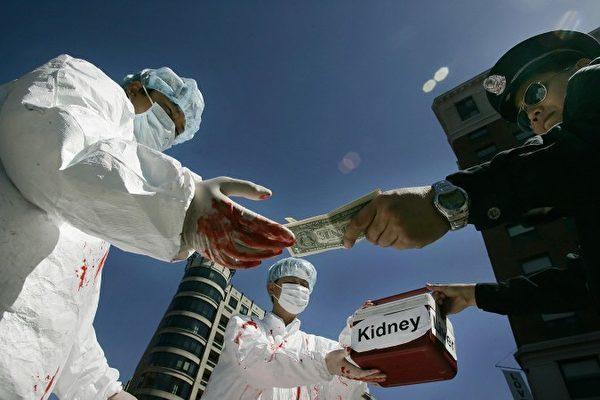 2006年4月19日,在美國首都華盛頓,法輪功學員於反迫害活動中模擬展示中國非法器官交易。(Getty Images)