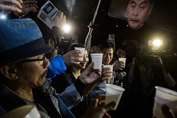 民主派人士遊行至禮賓府後,開香檳並高唱《喜氣洋洋》,慶祝特首梁振英宣佈不競選連任。(AFP/Getty Images)