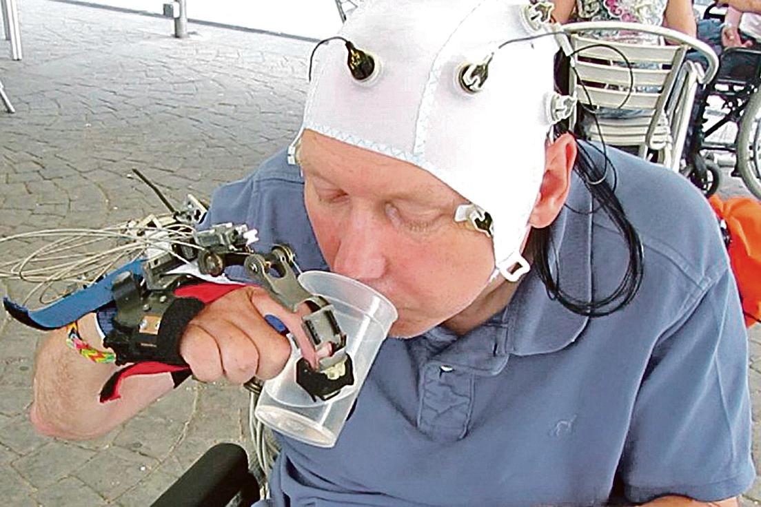 新型機械手,無需接受移植,只需戴上簡單裝置,即可藉著控制大腦意念協助脊椎損傷患者執行日常簡單動作,握叉子或拿水杯喝水都沒問題。(網絡截圖)