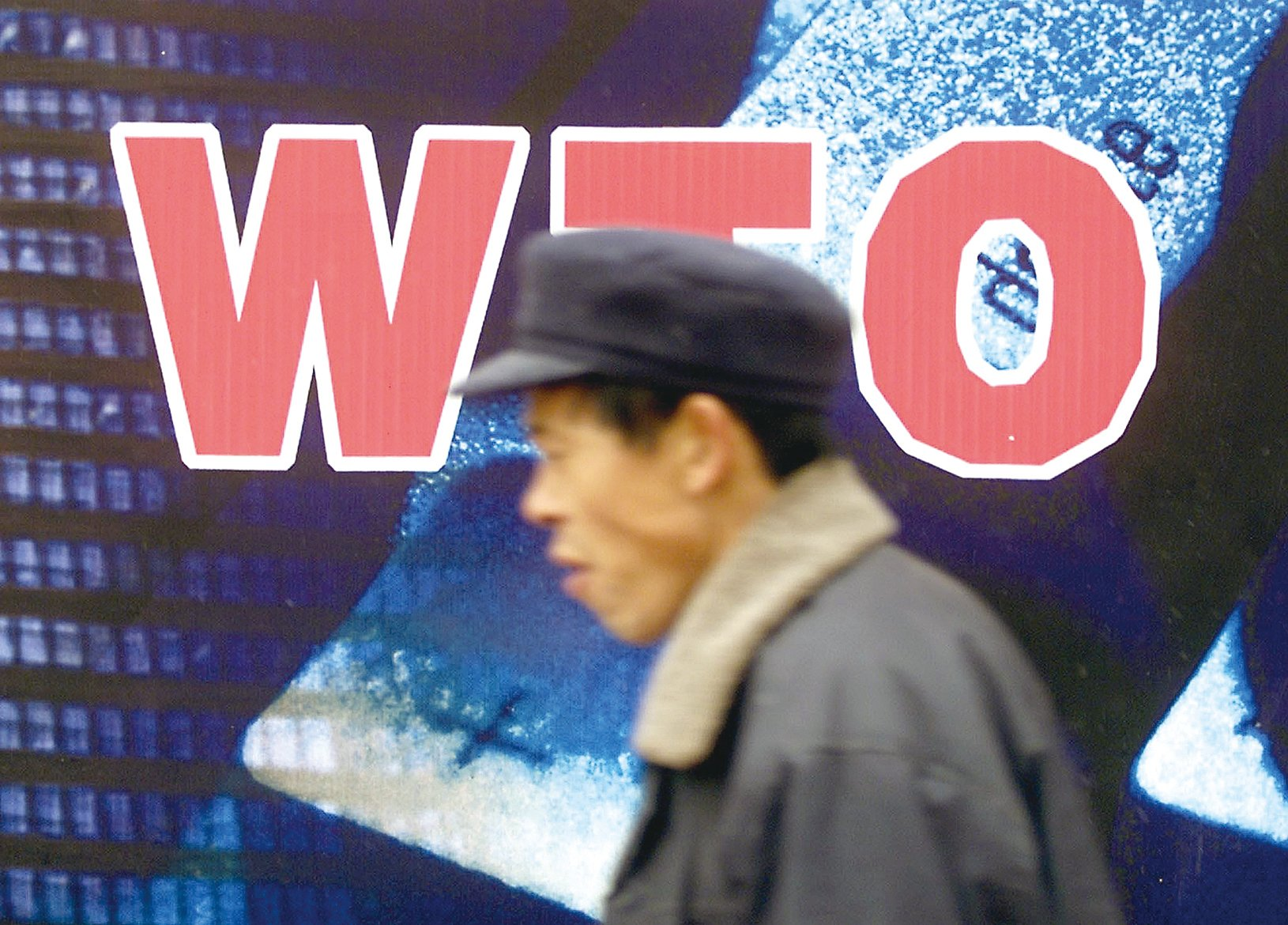 2001年「入世」以來中國已經發生了巨大的變化,但外界認為中共全面干預經濟的體制本質並未改變。這讓中國獲得「市場經濟地位」的努力遭遇挫折。圖為2001年12月10日中國「入世」前一天北京街頭。(AFP)