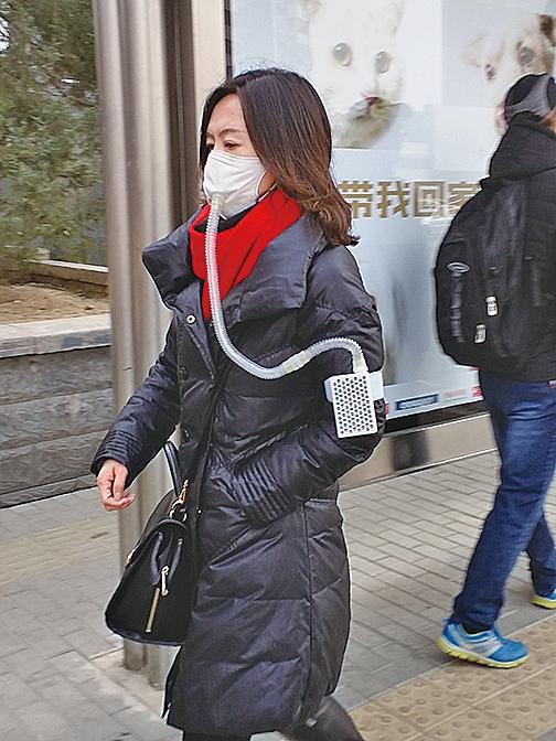 中國眾多地區陰霾持續不散,有民眾戴著連接迷你「空氣淨化器」的「防霾口罩」上街。(大紀元資料圖片)