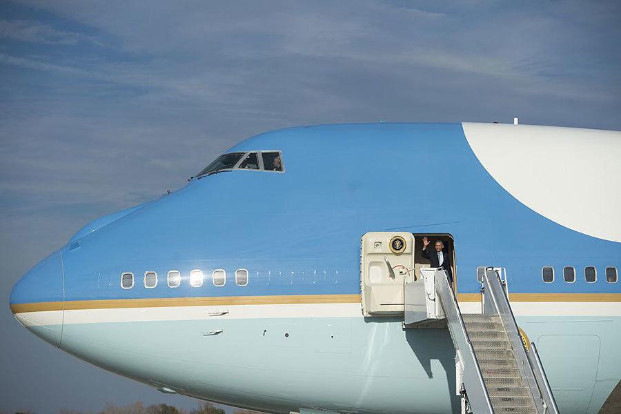 美國現任總統奧巴馬搭乘空軍一號,向地面人員招手。(SAUL LOEB/AFP/Getty Images)