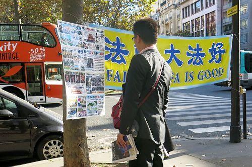 來巴黎旅遊的中國大陸遊客經過世界著名的埃菲爾鐵塔附近的法輪功真相點時,許多人駐足閱讀真相展板,了解真相。