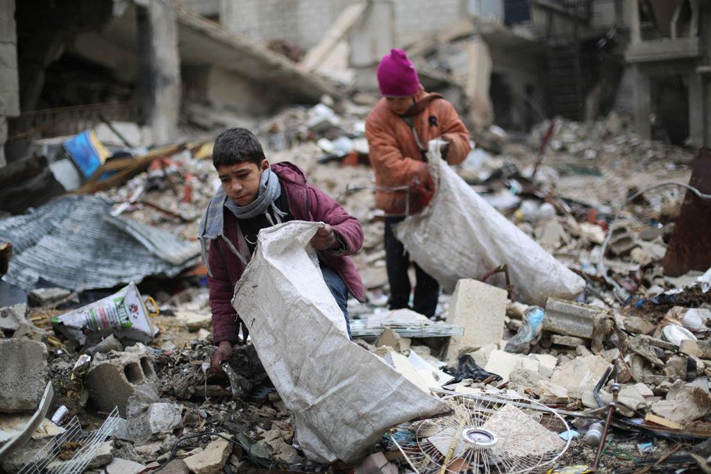 在土耳其和俄羅斯的斡旋下,敘利亞政府軍同反抗軍達成了全國停火協議,將於當地時間30日零點實現停火。圖為敘利亞男孩從建築倒塌的廢墟中撿木材,用於生火取暖和做飯。(AMER ALMOHIBANY/AFP/Getty Images)