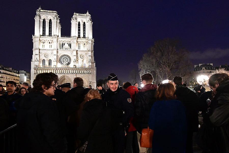 圖為12月24日,法國警察在巴黎聖母院前對遊客進行安全檢查。(MIGUEL MEDINA/AFP/Getty Images)