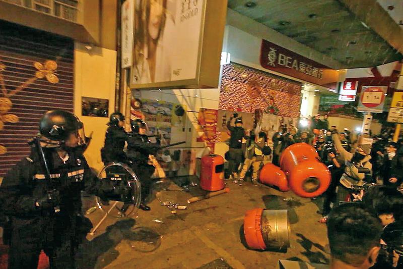 香港大年初二凌晨爆發嚴重衝突,警方向示威者噴射胡椒噴霧、向天開槍示警,示威者則以磚頭回擊,在街道燃燒雜物等。(潘在殊/大紀元)