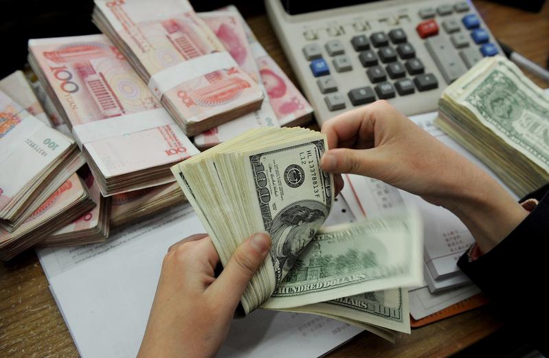 人民幣兌美元匯率經過1月4日和5日的暴漲後,重又下跌,學者預計2017年人民幣將繼續有貶值壓力。(STR/AFP/Getty Images)