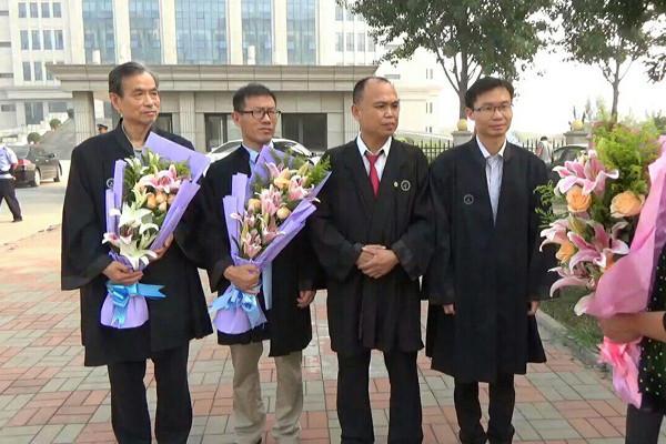 大陸四名律師(左一張讚寧律師、左二常伯陽律師、右一為張科科律師、右二為余文生律師)為法輪功學員周向陽、李珊珊案當庭做無罪辯。開庭結束後,法輪功學員家屬向四位律師獻花表示感謝。(知情者提供)