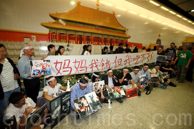 支聯會約50人到港鐵香港站的故宮廣告壁前悼念六四。(潘在殊/大紀元)