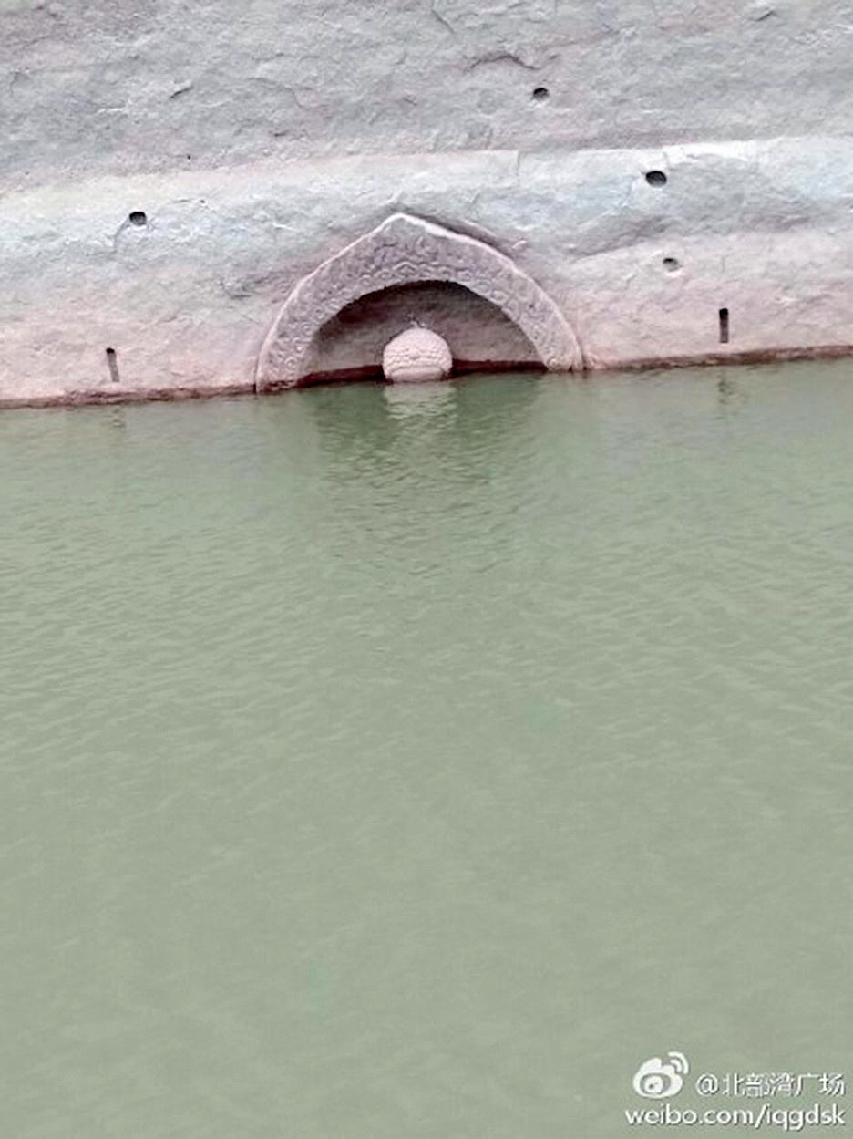 水庫水位降低後,一尊佛像的頭部浮出水面。(網絡圖片)