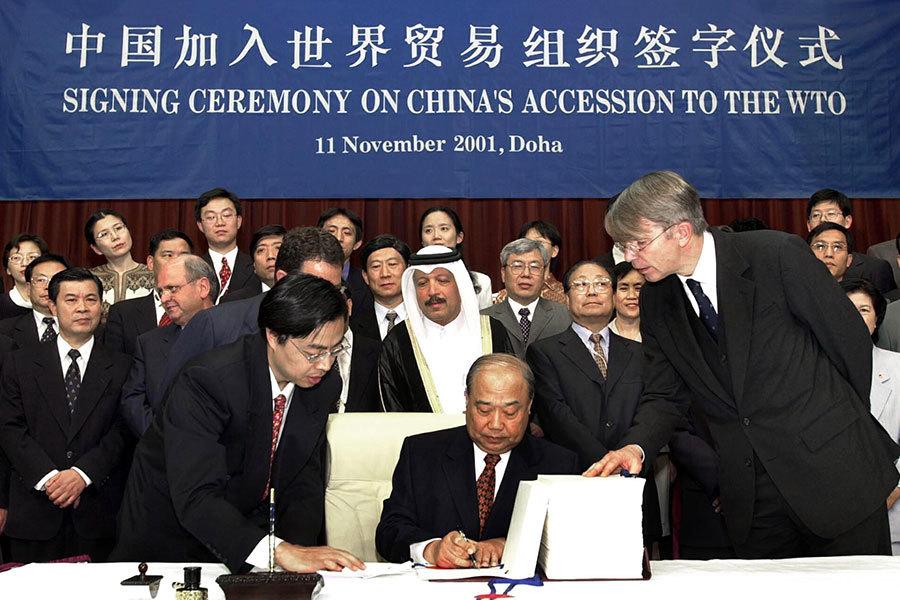 圖為2001年中共代表在多哈簽署加入世貿的簽字儀式。(HUSSEIN MALLA/AFP/Getty Images)