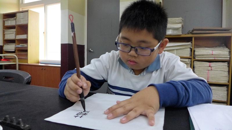 就讀台灣彰化社頭鄉舊社國小三年級的柳宇祐,以書法寫下自嘲言語在Facebook上爆紅。(讀者提供)