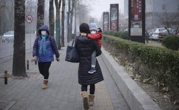 去年12月中旬起,大陸持續的嚴重陰霾污染,嚴重影響交通和民眾的健康。圖為北京一母親抱女兒往醫院。(Getty Images)