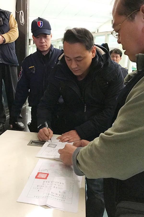 白狼張安樂兒子張瑋(右二)昨返台,即收到傳票並送往地檢署偵辦。(中央社)