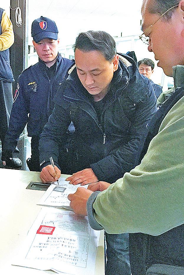 「白狼」張安樂兒子張瑋(中)15日返回台灣,即收到傳票並送往地檢署偵辦。(中央社)
