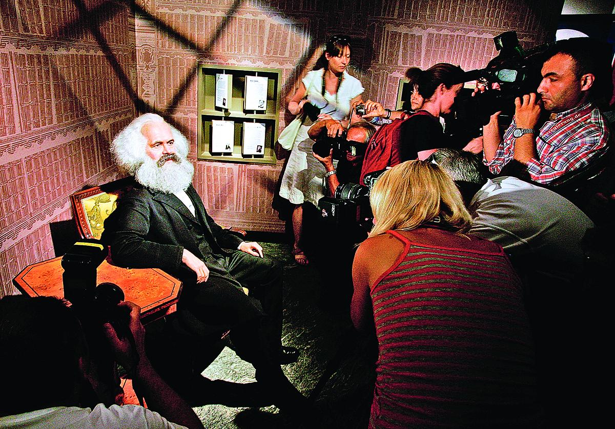 記者在對卡爾.馬克思在杜莎夫人蠟像館的柏林分部的蠟像拍照。(Getty Images)