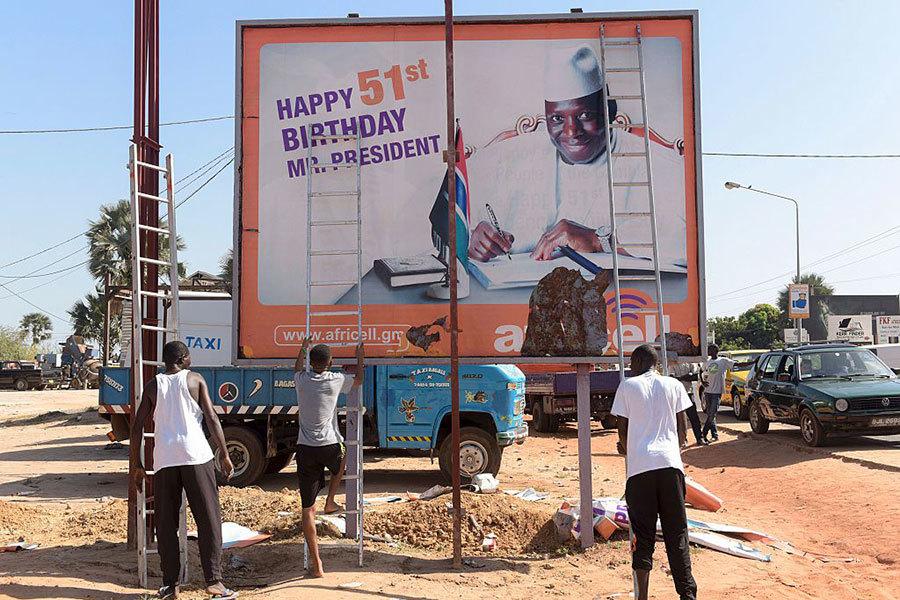 去年12月初選舉結束後,在一條街上,工人們準備撤除總統賈梅(Yahya Jammeh)的競選海報,當時賈梅在電視上承認敗選。(SEYLLOU / AFP / Getty Images)