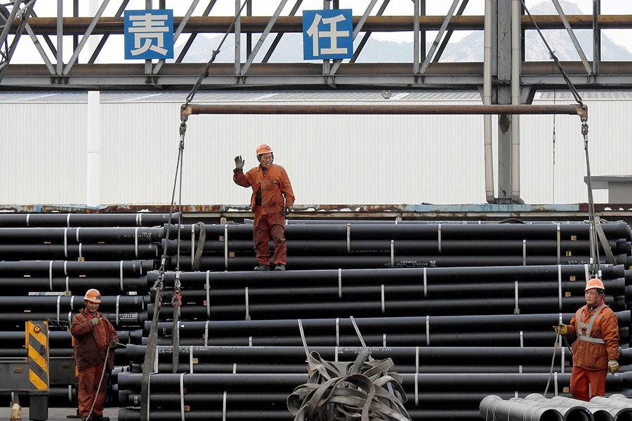 中國鋼鐵業勞工正在準備將鋼管裝載到卡車上。(STR/AFP/Getty Images)