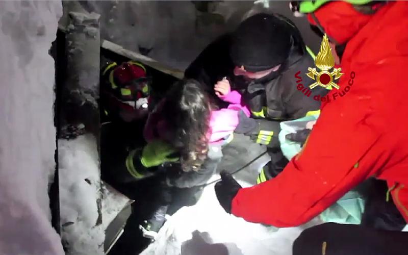 2017年1月20日,意大利里格皮亞諾酒店被厚雪掩埋,一個孩子(中)被救援人員從雪洞里救出來。(Handout/Vigili del Fuoco/AFP/Getty Images)