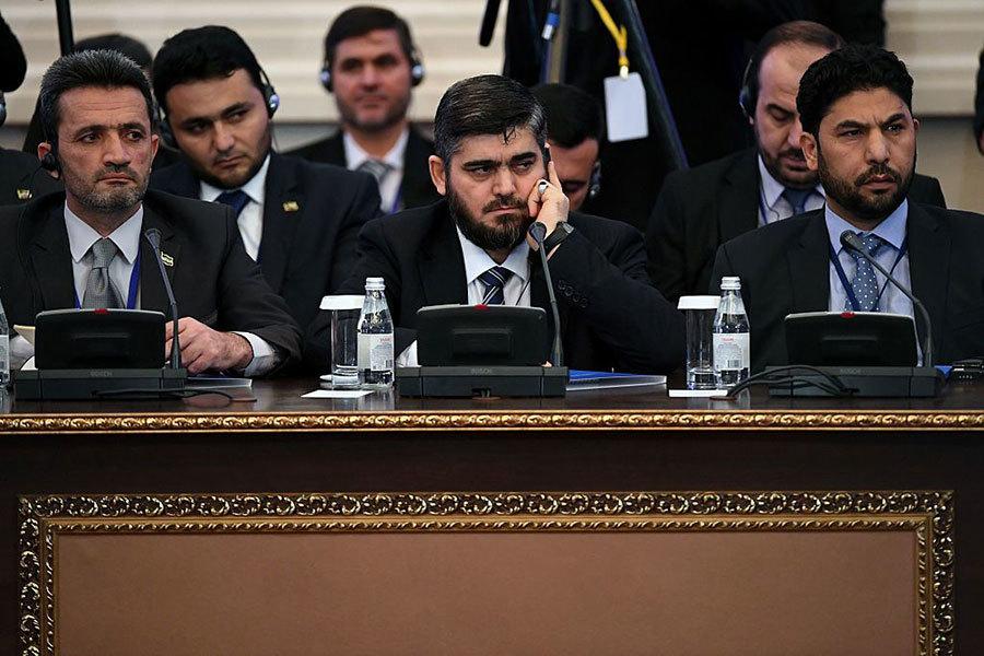 來自伊斯蘭軍反政府武裝的敘利亞反對派代表Mohammad Alloush (中) 。(AFP/Getty Images)
