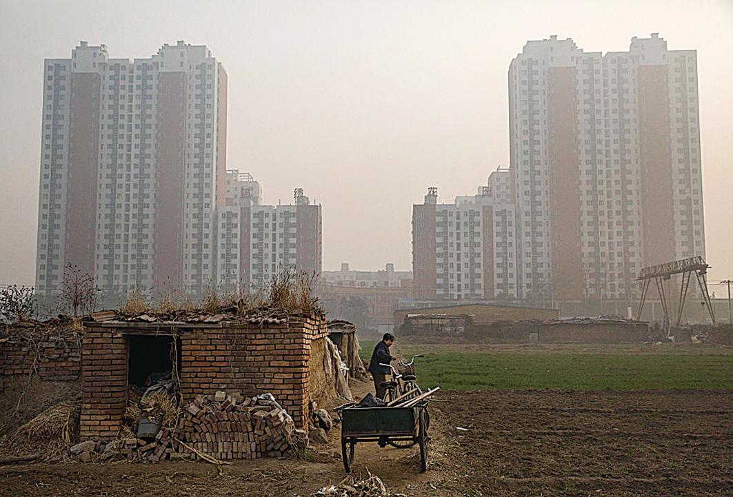一位農婦站在她位於北京市郊的農地上,農地周邊已經建滿大量的住宅。(Getty Images)