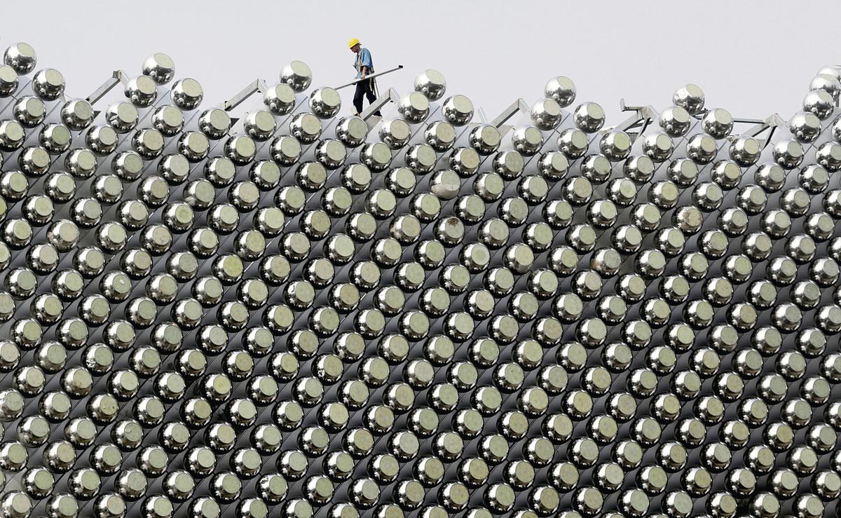 中國的房地產泡沫,是畸形政治的產物,也在腐敗政治中成長,最後也必須從政治上加以解決。圖為一個建築工人在武漢萬達瑞華酒店樓頂上工作。 (Getty Images)