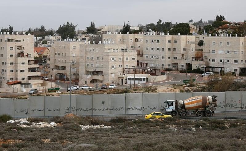 以色列政府24日批准了在約旦河西岸建設2500個定居點房屋計劃。圖為圍牆後面猶太人定居點拜特埃勒。(ABBAS MOMANI/AFP/Getty Images)