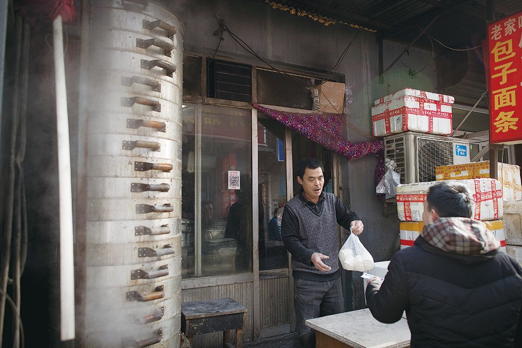 在民以食為天的中國,食的不公和毒食品對民眾造成嚴重的威脅。圖為今年1月18日一顧客在北京街頭的一家外賣麵食的小店買饅頭。(AFP/Getty Images)