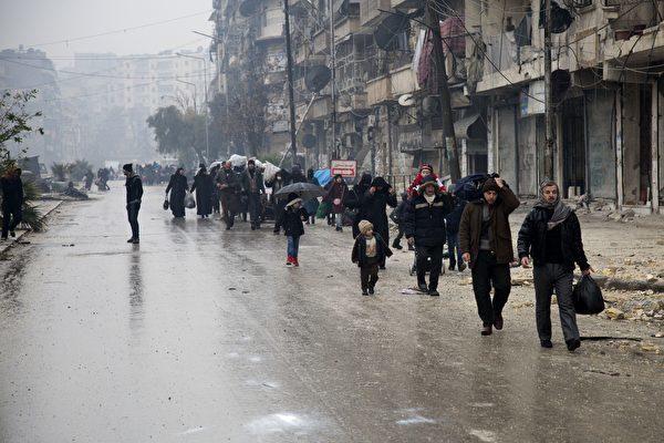 圖為上月平民和戰士從敘利亞第二大城市阿勒頗(Aleppo)反抗軍仍然控制的地區撤離。(KARAM AL-MASRI/AFP/Getty Images)