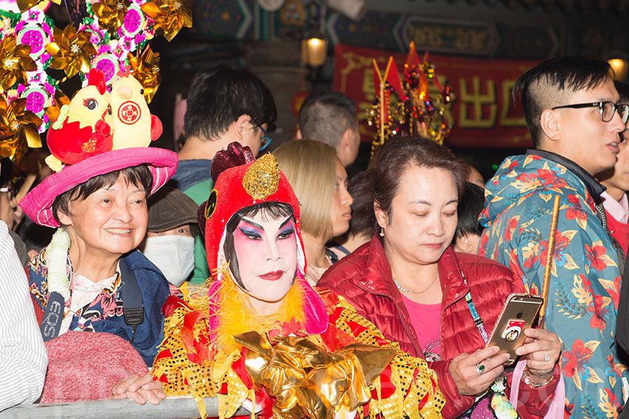 周潤發的姊姊周聰玲(左一)戴上趣致雞帽,陪同藝人黃夏蕙(左二)搶上頭炷香。黃夏蕙今年以一身金雞打扮亮相。(郭威利/大紀元)