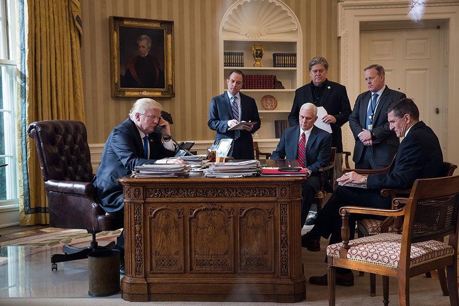 2017年1月28日,特朗普一日內接連與日本、德國、俄羅斯、法國和澳洲五國領導人通電話。圖為在白宮橢圓辦公室內接電話的特朗普。辦公室內除了特朗普外,自左至右的是白宮幕僚長普利巴斯、副總統彭斯、高級顧問班農和白宮發言人斯派塞以及國防高級顧問弗林。(Drew Angerer/Getty Images)