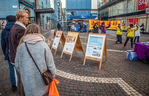 在斯德哥爾摩繁華的鬧市區(Hotorget)法輪功學員舉辦弘法講真相活動,民眾觀看真相展板,了解真相。(明慧網)