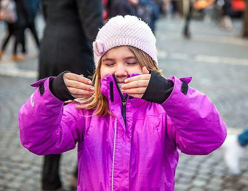 瑞典女孩索菲亞(Sofia)與法輪功學員一起抱輪(第二套功法),她雙目微閉,臉上帶著微笑。(明慧網)