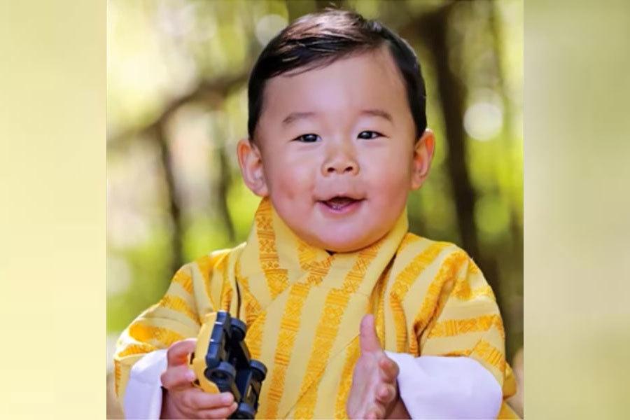 照片中的小王子手拿玩具車,身穿黃色不丹傳統服飾,超萌可愛。(視像擷圖)