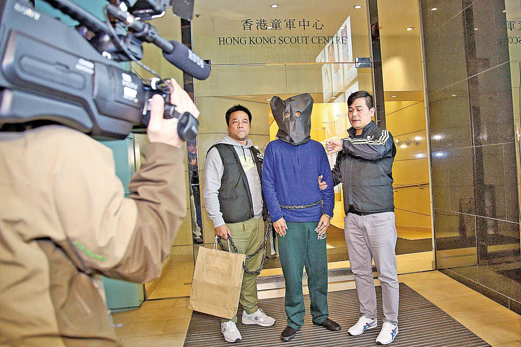 運輸工陳基成(右二戴黑頭套者)承認去年在尖沙咀龍堡國際賓館男廁內放置假炸彈,被重判入獄兩年。(大紀元資料圖片)