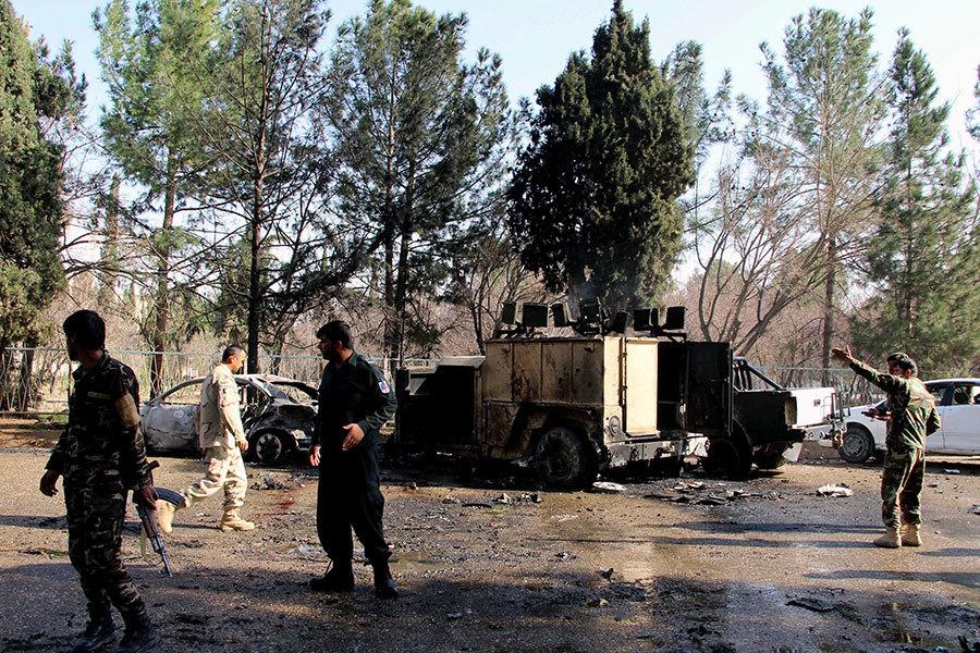 2017年2月11日,阿富汗赫爾曼德省首府拉什卡爾加發生汽車炸彈襲擊士兵事件,圖為爆炸過後現場殘留的汽車以及前來調查的士兵。(NOOR MOHAMMAD/AFP/Getty Images)