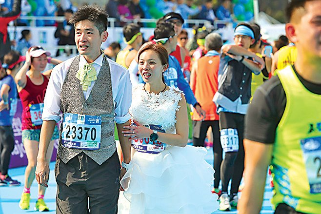 馮先生及準馮太穿婚紗參加全馬,寓意完成愛情長跑。(余鋼/大紀元)