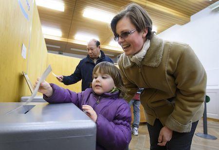 瑞士周日(2月12日)舉行公投,通過了放寬第三代移民入籍條件的法案。這將使在瑞士土生土長的第3代移民自動成為公民。圖為選民進行投票。(FABRICE COFFRINI/AFP/Getty Images)