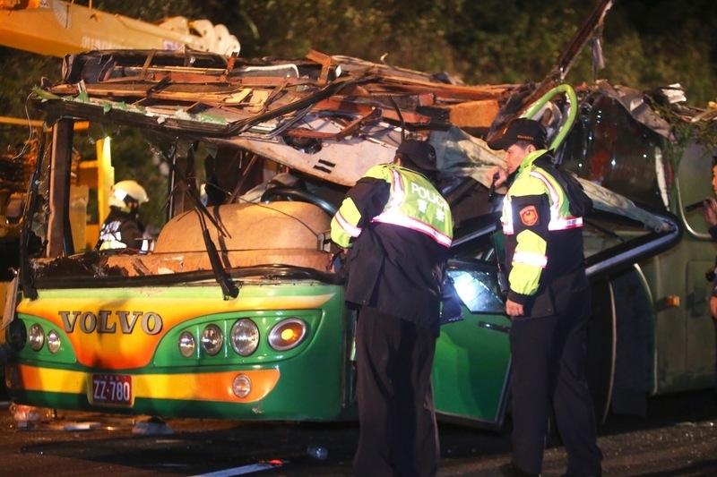 台灣一輛賞櫻團旅遊巴2月13日晚間在國道翻車,造成33人死亡、11人受傷。這也是30年來台灣最嚴重的公路事故。圖為翻覆的旅遊巴體扶正後,警方勘驗車體。(中央社)