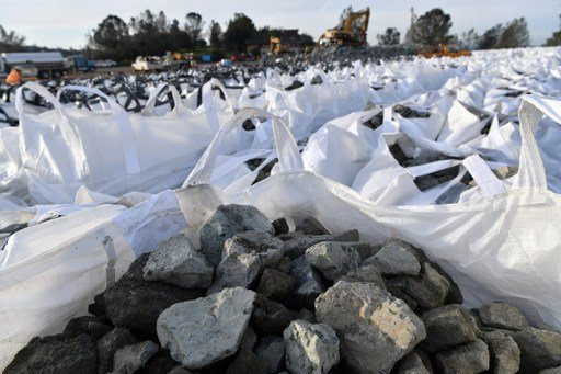 星期一下午,工作人員將裝滿岩石的大袋子放入緊急泄洪道邊緣的破損缺口,減少洪水通過山坡排放。(AFP PHOTO/Josh Edelson)